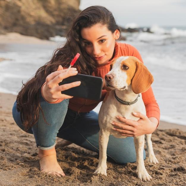 Mulher e cachorro tomando selfie Foto gratuita