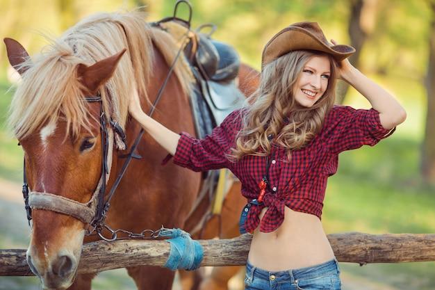 Mulher e cavalo estilo retrô do oeste selvagem Foto Premium