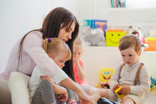 Mulher e filhos sentados no chão Foto Premium