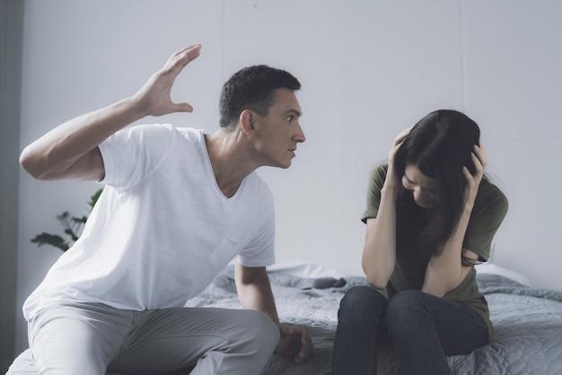 Mulher e homem brigas enquanto está sentado na cama em casa Foto Premium