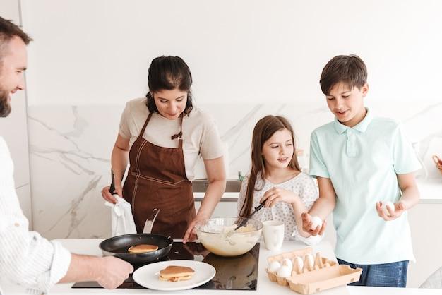 Mulher e homem com crianças felizes, menino e menina 8-10, cozinhando juntos e fritando panquecas no fogão moderno na cozinha Foto Premium