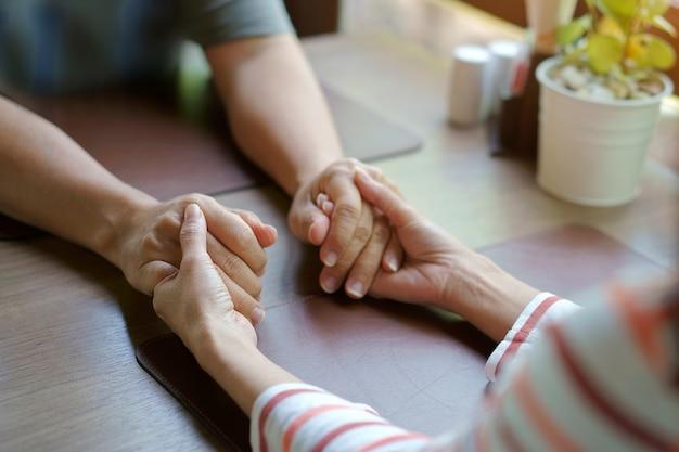 Mulher e homem de mãos dadas cuidar juntos Foto Premium