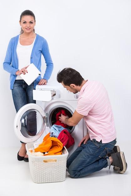 Mulher e homem estão lavando roupa com máquina de lavar roupa. Foto Premium