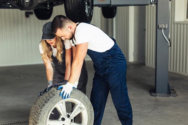 Mulher e homem no auto serviço mudando as rodas Foto gratuita
