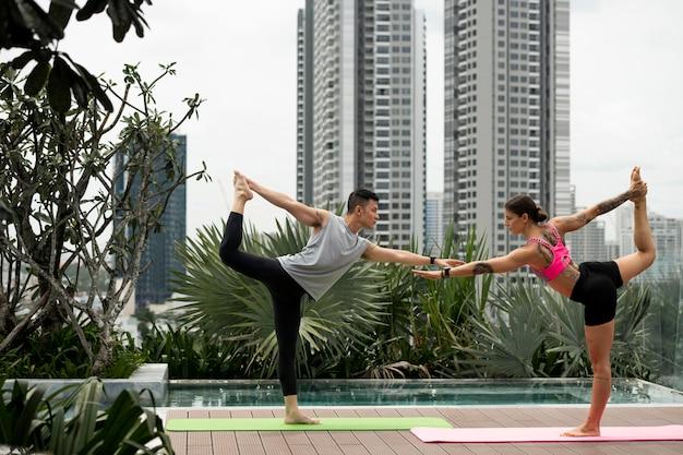 Mulher e homem praticando ioga no tapete ao ar livre ao lado da piscina Foto gratuita