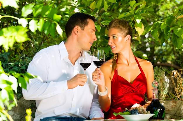 Mulher e homem sentado debaixo de videira e bebendo Foto Premium