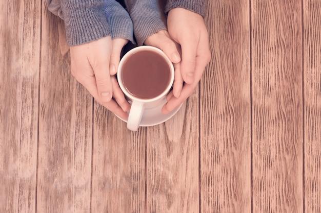 Mulher e mens mãos segurando uma xícara quente de chá na mesa de madeira Foto Premium