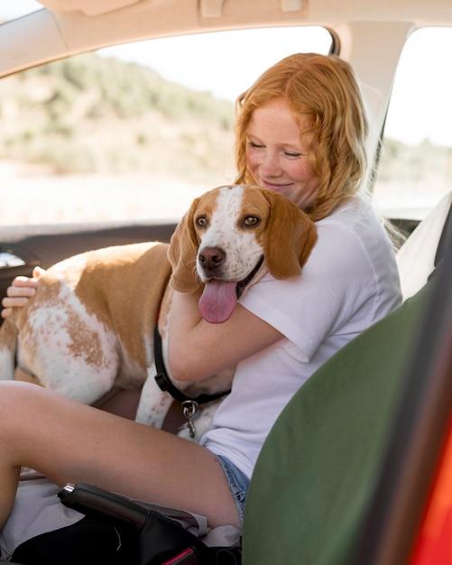 Mulher e o cachorro dela sentados no carro Foto gratuita