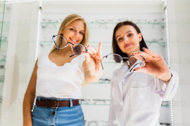 Mulher e oculista segurando armações de óculos Foto gratuita