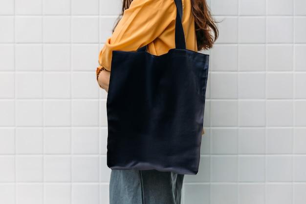 Mulher, é, segurando, saco preto, lona, tecido Foto Premium