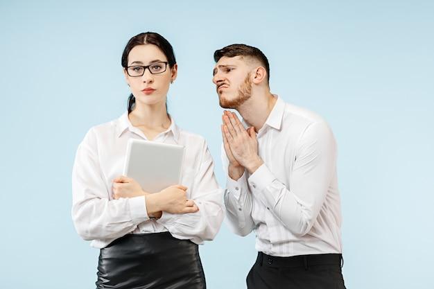 Mulher e sua secretária em pé no escritório ou estúdio. empresário implorando para seu colega. conceito de relacionamento no escritório, emoções humanas Foto gratuita