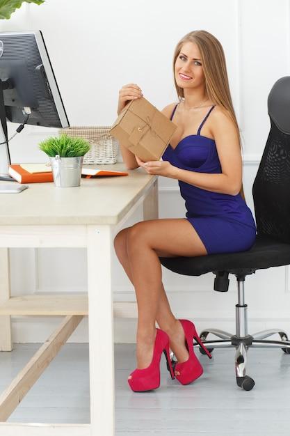 Mulher elegante abre um pacote Foto gratuita