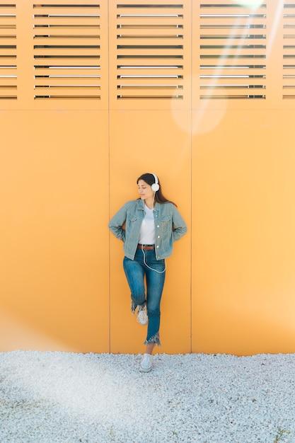 Mulher elegante, apoiando-se na parede amarela usando fone de ouvido Foto gratuita