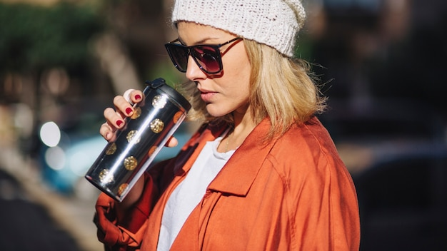 Mulher elegante bebendo bebida quente na rua Foto gratuita