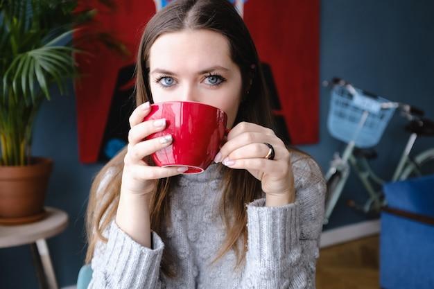 Mulher elegante bonita nova que senta-se em um café, guardando um copo do cappuccino, olhando a câmera, apreciando, rua da cidade, jantar romântico, ensolarada. menina tomando café. café da manhã. coffee break. Foto Premium