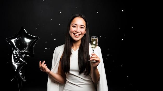 Mulher elegante, brindando com champanhe e balões Foto gratuita