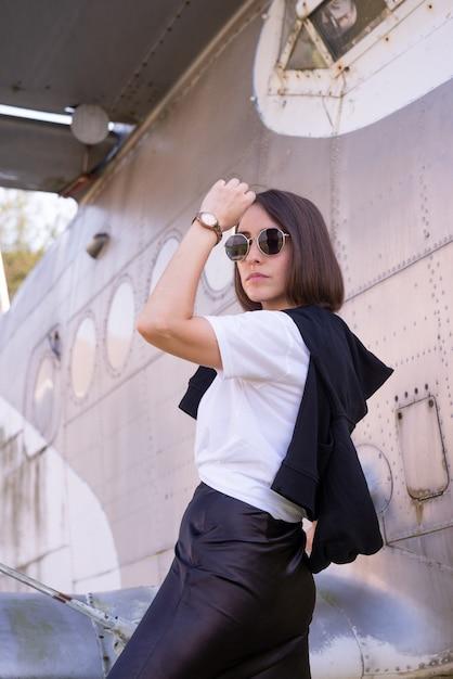 Mulher elegante com óculos e um relógio posando em um velho avião retrô Foto Premium