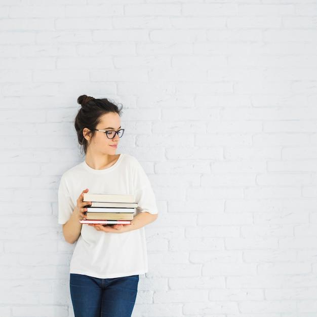 Mulher elegante com pilha de livros Foto gratuita