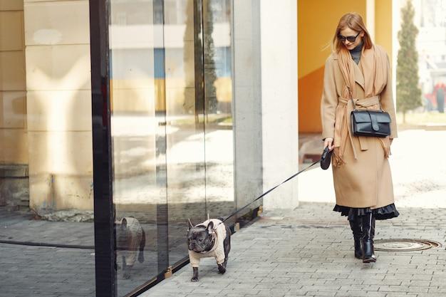 Mulher elegante com um casaco marrom com bulldog preto Foto gratuita