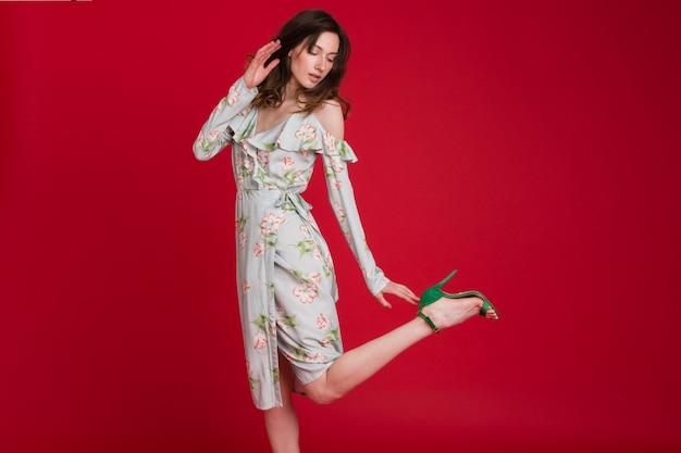 Mulher elegante com vestido de tendência da moda de verão posando em vermelho Foto gratuita