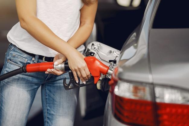 Mulher elegante, de pé em um posto de gasolina Foto gratuita