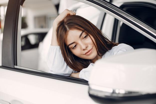 Mulher elegante e elegante em um salão de carro Foto gratuita
