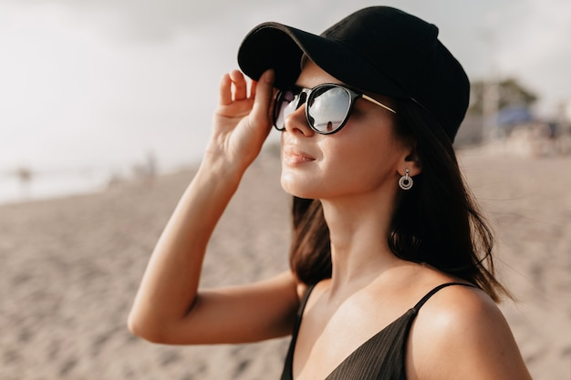 Mulher elegante e moderna em roupas da moda olhando para o oceano com um sorriso feliz usando boné e óculos e aproveita os dias quentes de verão. jovem modelo feminina, branca Foto gratuita