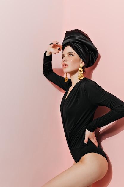 Mulher elegante em macacão preto posando na parede rosa Foto gratuita