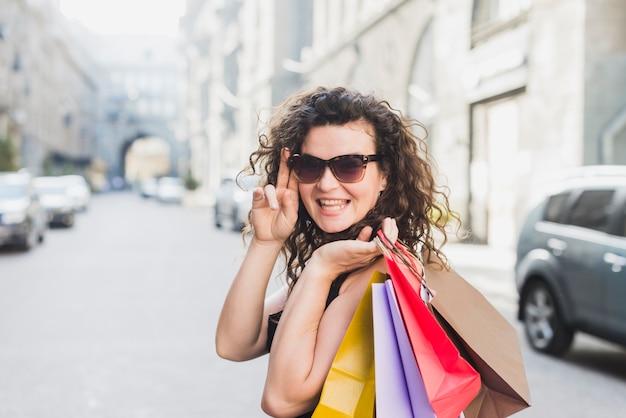 3c2d22996 Mulher elegante em óculos de sol, carregando sacolas de compras ...