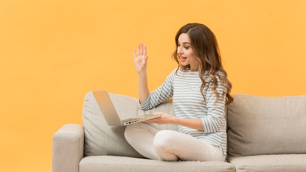 Mulher elegante, gravando-se no sofá Foto gratuita