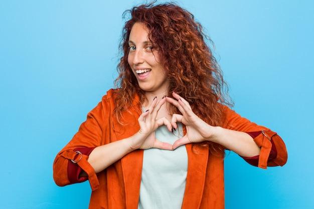 Mulher elegante jovem ruiva sorrindo e mostrando uma forma de coração com as mãos Foto Premium