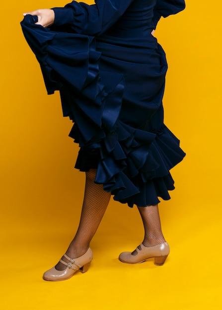 Mulher elegante, levantando o vestido com fundo laranja Foto gratuita
