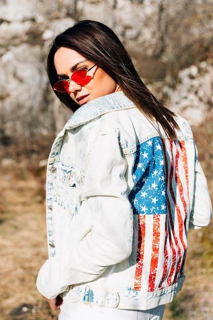 Mulher elegante na jaqueta jeans e óculos de sol Foto gratuita