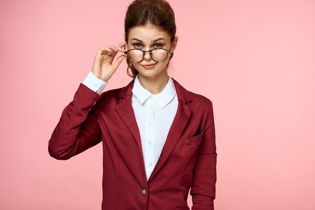 Mulher elegante na jaqueta vermelha óculos gerente de escritório fundo rosa. foto de alta qualidade Foto Premium