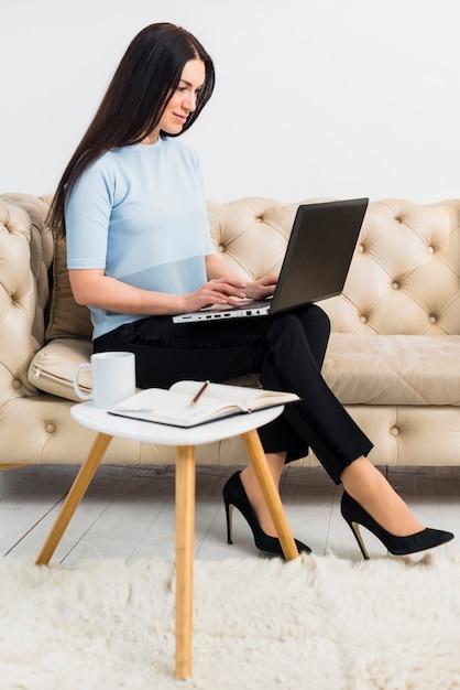 Mulher, em, azul, sentar sofá, com, laptop Foto gratuita