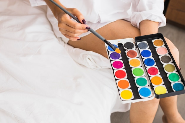 Mulher, em, branca, sentando, com, aquarela, pinturas, em, mãos Foto gratuita