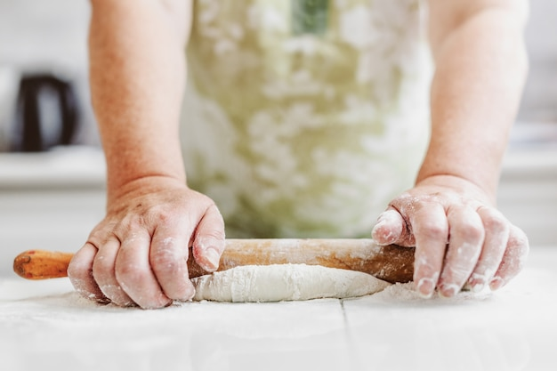 Mulher em casa amassando massa para cozinhar pão ou pizza. conceito de comida caseira. estilo de vida Foto gratuita