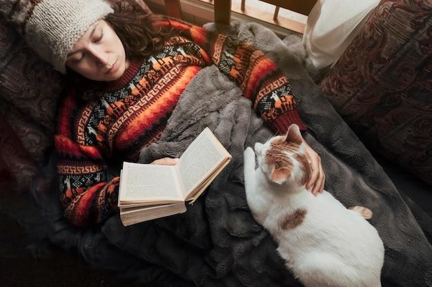 Mulher em casa deitada lendo um livro acariciando seu gato. conceito de passatempos e estar em casa. Foto Premium