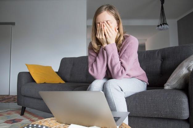 Mulher em casa fechando os olhos com as mãos, pensando. laptop na mesa Foto gratuita