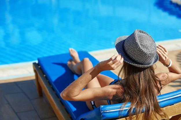 Mulher, em, chapéu, mentindo, ligado, um, lounger, perto, a, piscina, em, a, sunbathes hotel Foto Premium