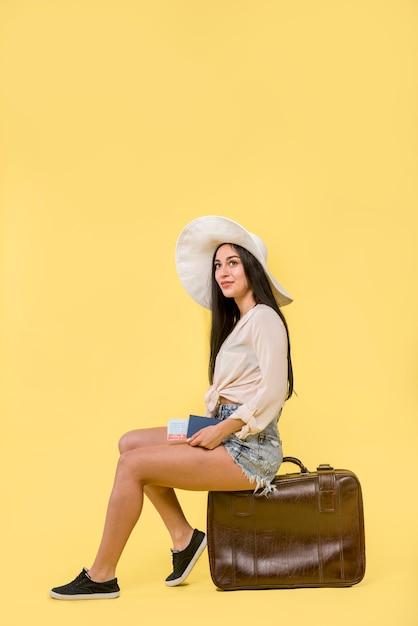 Mulher, em, chapéu, sentando, ligado, marrom, mala Foto gratuita