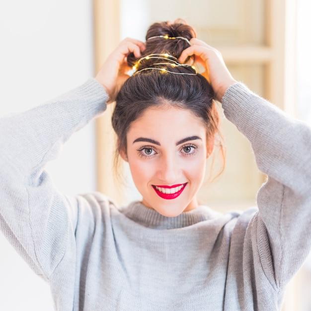 Mulher em cinza com guirlanda de iluminação no cabelo Foto gratuita