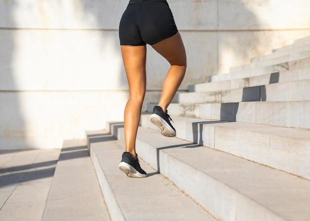 Mulher em close-up correndo na escada Foto gratuita