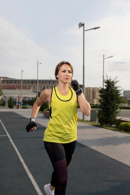 Mulher em equipamentos de esporte amarelo e preto treinando, correndo na rua. Foto gratuita