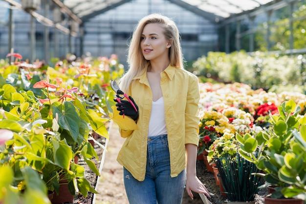 Mulher em estufa com tesoura de jardinagem Foto gratuita