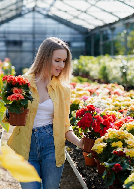 Mulher em estufa cuidando de flores Foto gratuita