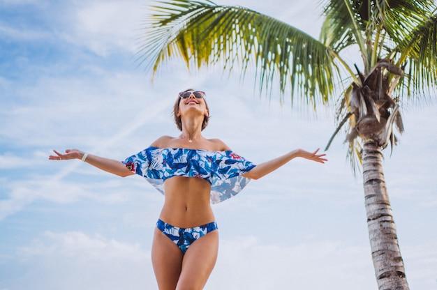 Mulher em fato de banho em pé na praia perto da palma da mão Foto gratuita