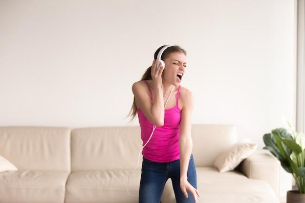 Mulher em fones de ouvido cantando e dançando em casa Foto gratuita