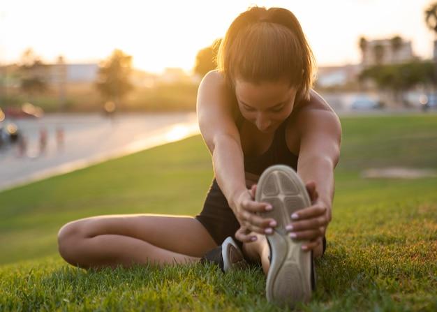 Mulher em foto completa esticando a perna Foto gratuita