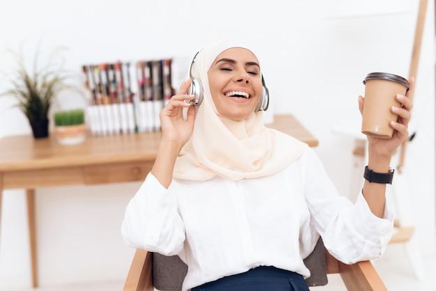 Mulher em hijab ouve música em fones de ouvido. Foto Premium